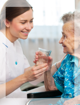 caretaker giving a glass of water to her patient