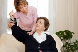 caretaker assisting her patient in exercise